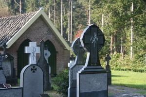 Gerenoveerde grafzerken met op de achtergrond het lijkenhuisje